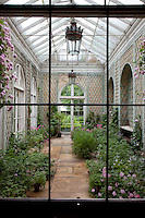 View through a window into the conservatory, its walls lined with mint green trellis. Two ceiling lanterns with ornate metal decoration hang from wrought iron rails above