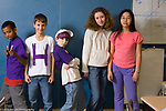 Group of 6th grade students posing in classroom, three boys and two girls