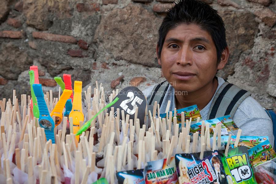 Antigua, Guatemala.  Young Man Selling Children's Watches and Refreshments, Plaza de  Armas.  Semana Santa.