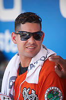 Norfolk Tides designated hitter Dariel Alvarez (12) in the dugout during a game against the Rochester Red Wings on July 17, 2016 at Frontier Field in Rochester, New York.  Rochester defeated Norfolk 3-2.  (Mike Janes/Four Seam Images)