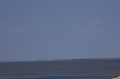 Faint view of a prairie town appears as a mirage across the miles of a lake and a salt flats.