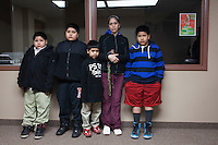 Manuela Maldona with four of her 6 children at an HOLA meeting in Painesville, Ohio. Her husband  Diego Maldonado was deported. She works 12 hours a day six days a week to support her children. The two eldest children also work factory jobs to help support the  family. Painesville, Ohio. Photo by Brendan Bannon. March 25, 2014