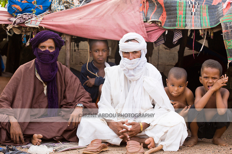A Touareg family sits in front of their tent in Ouagadougou, Burkina Faso.  The Touareg are traditionally nomadic, traversing the deserts of Mauritania, Mali, Niger, Chad, Libya, and Algeria. Traditionally, the roof of the tent would be pieced together from leather animal hides, but this family in Ouagadougou has made a roof of more modern materials.