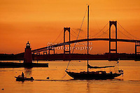 The sky glows orange over Goat Island Lighthouse and the Newport Bridge