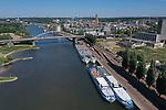Foto: VidiPhoto<br /> <br /> ARNHEM/DODEWAARD - Cruiseschepen en rondvaartboten liggen al anderhalve maand werkloos aan de Rijnkade in Arnhem (foto) en in de Waalhaven bij Dodewaard. Vanwege de coronamaatregelen mogen er voorlopig geen passagiers aan boord en varen de schepen niet. In Arnhem liggen vooral cruiseschepen van Nederlandse maatschappijen. Bij de gemeente Arnhem hebben zij inmiddels een verzoek ingediend om geen liggeld te hoeven betalen. De haven van Dodewaard is voorlopig de ankerplaats voor de vloot toeristenschepen die normaal op de Europese rivieren vaart. Een deel van de schepen is eigendom van Scylla AG, een rederij uit Zwitserland die op verschillende Europese rivieren vaart. De totaal 32 schepen van de vloot liggen allemaal stil in verschillende havens. De schepen zelf hebben net hun grote winter-onderhoudsbeurten gehad.