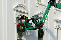 A worker installs holiday wreaths on the White House in Washington, DC on November 21, 2020.  <br /> Credit: Chris Kleponis / Pool via CNP /MediaPunch