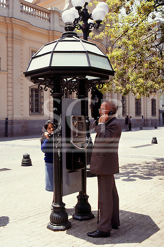 Santiago, Chile. Man using telephone in booth.