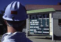 SUDAFRICA - Kimberley, miniera di diamanti di Bultfontein ( Miniere De Beers): il cartello con l'indicazione degli infortuni. Un lavoratore di spalle con un elmetto azzurro.