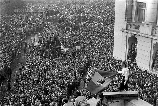 ROMANIA, Pta. Palatului, today Pta. Revolutiei, Bucharest, 22.12.1989<br /> People rise against Ceausescu. After the Ceausescu couple has fled by helicopter around noon, protestors fill the square which originally was guarded by tanks. They aim at the Communist Party Central Committee building. Its balcony is climbed, revolutionary speeches are made. Girl with national flag.<br /> © Andrei Pandele / EST&OST