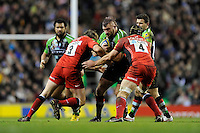 Joe Marler of Harlequins is tackled by Carlos Nieto (left) and Steve Borthwick of Saracens during the Aviva Premiership match between Harlequins and Saracens at Twickenham on Tuesday 27 December 2011 (Photo by Rob Munro)