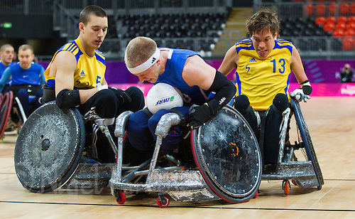18 APR 2012 - LONDON, GBR - Great Britain's Aaron Phipps (GBR) (Class 3.5) (centre) scores despite challenges from Sweden's Tomas Hjert (SWE) (Class 2.5) (left) and Stefan Jansson (SWE) (right) during their London International Invitational Wheelchair Rugby Tournament match at the Olympic Park Basketball Arena in Stratford, London, Great Britain  (PHOTO (C) 2012 NIGEL FARROW)