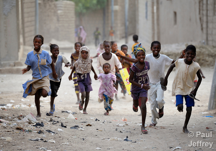 Children run through the street early on a Friday morning in Timbuktu, the northern Mali city that was seized by Islamist fighters in 2012 and then liberated by French and Malian soldiers in early 2013. During the jihadis' rule, girls and women could not appear in public unless they were completely covered. On Friday mornings the children make the rounds of houses where they receive sweets.