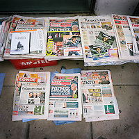 Newspapers and magazines displayed on the pavement, all running stories about the financial crisis.