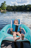 Little boy reading a book while floating in an inner tube on a public lake
