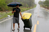 Omar Mejia, a resident in a nearby neighborhood, removes a trash can Wednesday, April 28, 2021, that had been washed onto W. Monroe Avenue in Lowell because of flash flooding. The National Weather Service office in Tulsa said the storm system that began moving through Northwest Arkansas Tuesday night had dropped from 1 to 3 inches of rain across the area by mid-morning Wednesday. With rainfall of 4 to 6 inches being reported in some areas. Check out nwaonline.com/210429Daily/ and nwadg.com/photos for a photo gallery.<br /> (NWA Democrat-Gazette/David Gottschalk)