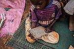 """CAR, Yelloke: A young boy is reading arabic on a wood tablet in his town in Yelloke. After the crisis in CAR, the anti-balaka of Yelloke city have decided to build a village where the muslim minority, the Peuls, can live and be protected by the UN.  23th April 2016. <br /> <br /> RCA, Yelloke: un jeune garçon lit de l'arabe sur une tablette en bois dans son village à Yelloke. Après la crise de Centrafrique, les anti-balaka ont décid"""" de construire un village pour la minorité musulmane, les peuls, où ils peuvent vivre et être protégés par l'UN.  23 avril 2016."""