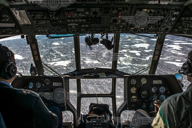 Pilots fly their helicopter above the frozen taiga.