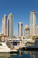 Dubai.  Luxury motor cruisers moored at Dubai Marina with apartment tower blocks in the background...