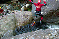 Switzerland. Canton Ticino. Corippo lies in the Verzasca valley. Canyoning activities in the river. A man with a red wet suit and a helmet is jumping from a rock into the water. With a population of just 16, Corippo is the smallest municipality in Switzerland. Despite this, it possesses the trappings of communities many times its size such as its own coat of arms. The village has maintained its status as an independent entity since its incorporation in 1822. 9.05.13 © 2013 Didier Ruef