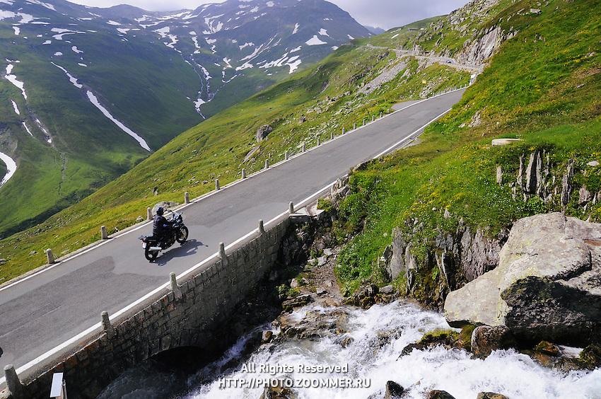 Perspective of Alpine road with biker