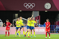 YOKOHAMA, JAPAN - AUGUST 6: Stina Blackstenius #11 of Sweden celebrates scoring with her teammates while Jessie Fleming #17 of Canada goes by dejected during a game between Canada and Sweden at International Stadium Yokohama on August 6, 2021 in Yokohama, Japan.