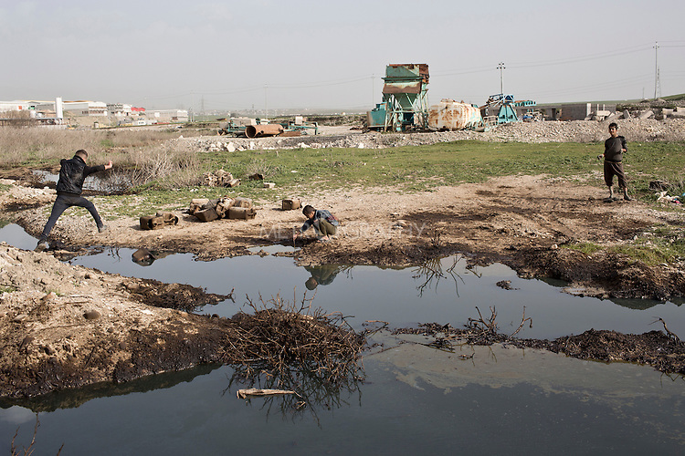 15/02/15 --TANJERO, IRAQ: Sardesht (13), Ezidiar (9), and Jamal (17) play in polluted water near the banks of the Tanjero river.<br /> <br /> The family of Yezidis, displaced from Sinjar, live next to an oil refinery in the Kurdish Region of Iraq. The young men run the refinery 24 hours a day with little to no safety equipment. Reporting for this article was supported by a grant from the Pulitzer Center on Crisis Reporting