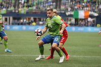 SEATTLE, WA - NOVEMBER 10: Jordan Morris #13 of the Seattle Sounders FC shields the ball from Nicolas Benezet #7 of Toronto FC during a game between Toronto FC and Seattle Sounders FC at CenturyLink Field on November 10, 2019 in Seattle, Washington.