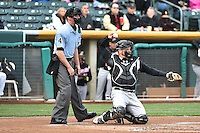 Home plate umpire Scott Mahoney (4) and Stephen Vogt (26) of the Sacramento River Cats during the game against the Salt Lake Bees at Smith's Ballpark on April 3, 2014 in Salt Lake City, Utah.  (Stephen Smith/Four Seam Images)