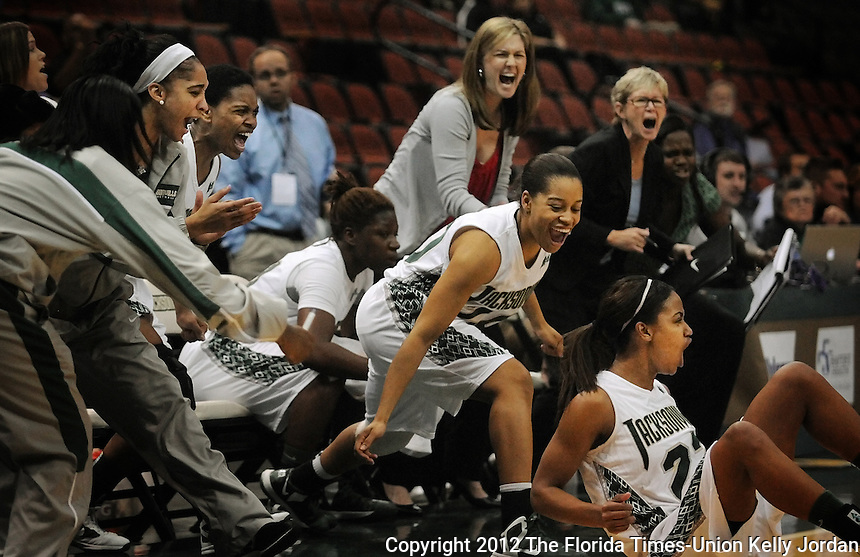 Kelly.Jordan@jacksonville.com--121812--The Jacksonville University womens basketball team bench errupts with cheers led by Ciara McLee, (20), center as their teammate Tracie Sneed, (22), falls on the floor towards them after scoring a three point shot to tie the game and send it into overtime as the Jacksonville University Dolphins womens basketball team take on Troy University at Veterans Memorial Arena in Jacksonville, Florida Tuesday night December 18, 2012. The lady dolphins lost to Troy in overtime.(The Florida Times-Union, Kelly Jordan)