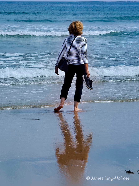 Beach scene with a rear view of a bare-footed mIddle-aged woman standing at the water's edge with her shoes in one hand.
