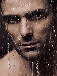 Man face wet from water pouring on it, artistic dramatic portrait. Image © MaximImages, License at https://www.maximimages.com