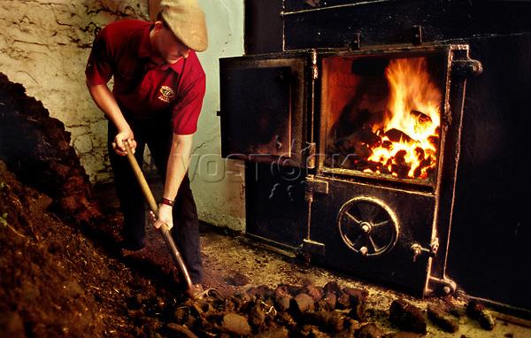 Europe, Great Britain, Scotland, Whisky Production, Isle of Islay, Bowmore distillery, peat fire for drying malt, malthouse, peat fired kiln, fire-place,stove, workman, destillery.- Europa, Grossbritannien, Schottland, Whisky-Produktion, Isle of Islay, Bowmore Destillerie, Torffeuer zur Gerste-Keimung, Maelzerei, Whisky-Brennerei, Whiskey, Whisky, Whiskeyproduktion, Arbeiter, Torf, Ofenfeuer, offener Kamin, Single Malt Whisky.15.08.2003. Copyright: Dorothea Schmid / Agentur laif(Bildtechnik: sRGB, 51.79 MByte vorhanden)