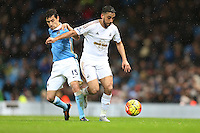 Jesus Navas competes with Neil Taylor during the Barclays Premier League Match between Manchester City and Swansea City played at the Etihad Stadium, Manchester on 12th December 2015