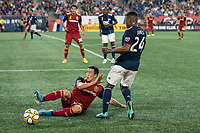 FOXBOROUGH, MA - SEPTEMBER 21: Brooks Lennon #12 of Real Salt Lake slides to tackle DeJuan Jones #24 of New England Revolution during a game between Real Salt Lake and New England Revolution at Gillette Stadium on September 21, 2019 in Foxborough, Massachusetts.