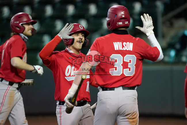 Brent Todys (12) of the Ohio State Buckeyes, left, is greeted by Sam Wilson after scoring an insurance run in the 13th inning of a 6-3 win over the Illinois Fighting Illini on Friday, March 5, 2021, at Fluor Field at the West End in Greenville, South Carolina. (Tom Priddy/Four Seam Images)