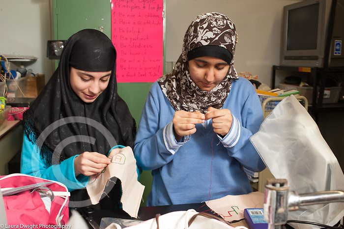 Education High School sewing elective two girls sewing both wearing head scarves, one threading needle