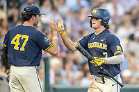 Michigan Wolverines outfielder Jesse Franklin (7) is greeted by teammate Tommy Henry (47) after scoring against the Vanderbilt Commodores during Game 3 of the NCAA College World Series Finals on June 26, 2019 at TD Ameritrade Park in Omaha, Nebraska. Vanderbilt defeated Michigan 8-2 to win the National Championship. (Andrew Woolley/Four Seam Images)