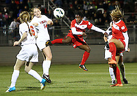 BOYDS, MARYLAND - April 06, 2013:  Jasmyne Spencer (20) of The Washington Spirit heads past Emily Sonnett(16) and Kristen McNabb (14) of the University of Virginia women's soccer team in a NWSL (National Women's Soccer League) pre season exhibition game at Maryland Soccerplex in Boyds, Maryland on April 06. Virginia won 6-3.