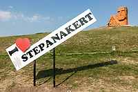 """Nagorno-Karabakh, also known as Artsakh, is a landlocked region in the South Caucasus. Stepanakert is the capital and the largest city of the Republic of Artsakh (better known as Nagorno-Karabakh). An advertising sign with the words written in english """" I love Stepanakert"""". """"We Are Our Mountains"""" is a large monument north the city. The sculpture, completed in 1967 by Sargis Baghdasaryan, is widely regarded as a symbol of the Armenian heritage of Nagorno-Karabakh. The monument is made from volcanic tufa and depicts an old man and woman hewn from rock, representing the mountain people of Karabakh. It is also known as """"tatik-papik""""  in Armenian, which translates as """"Grandma and Grandpa"""". The sculpture is prominent in Artsakh's coat of arms. Nagorno-Karabakh is a disputed territory, internationally recognized as part of Azerbaijan, but most of the region is governed by the Republic of Artsakh (formerly named Nagorno-Karabakh Republic), a de facto independent state with Armenian ethnic population. Since 1994, regular peace talks between Armenia and Azerbaijan mediated by the OSCE Minsk Group have failed to result in a peace treaty. 7.10.2019 © 2019 Didier Ruef"""