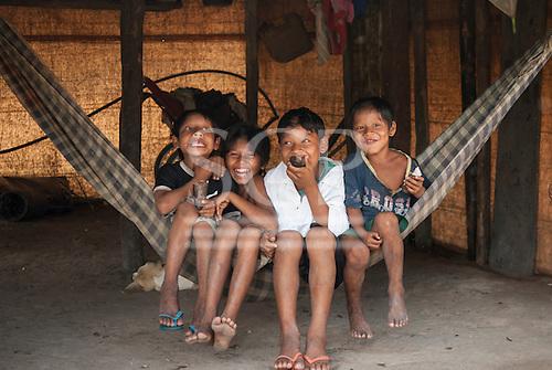 Aldeia Baú, Para State, Brazil. Four Kayapo boys sitting in a hammock, messing about.