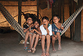 Aldeia Baú, Para State, Brazil. Four Kayapo boys sitting in a hammock, messing about.