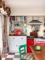 The cosy kitchen features a red Aga with a doorway leading to the conservatory graced with a pair of vintage chintz curtains