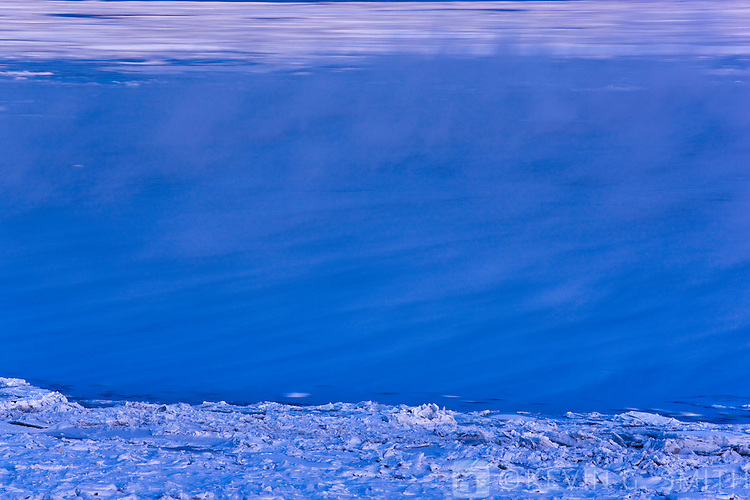 Steam rising off of the water of Knik Arm, ice floes blured moving in the background, Anchorage, Southcentral Alaska, USA,