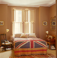 A double bed is situated under the custom-made shutters in the master bedroom and is covered by a vintage Union Jack throw whilist antique chairs are used as bedside tables with brass angle-poise lamps clamped on top