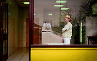 Woman looking out from Baxter's chip shop window, Long Sutton,Lincolnshire,UK