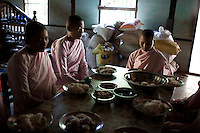 Nuns pray before eating lunch at a monastery in Mandalay. Buddhist nuns are not treated with the same reverence as their male counterparts, having to prepare their own food, and living in monasteries that are often pushed to the outskirts of town. The monasteries themselves are usually less well kept than the monks' monasteries due to a lack of funds...