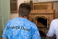 """Germany. Bayern state. The Dachau Concentration Camp Memorial Site. A young american boy, wearing a t-shirt of the music band """"The Grateful Dead"""", stands in front of one  the four ovens in the crematorium, the barrack X. .Still preserved today are the first crematorium built in 1940 and the so-called barrack X, built in 1942/43. The crematorium was used to dispose of the corpses from the concentration camp; the ovens were mostly in operation around the clock. On march 22, 1933, the first concentration camp was opened in Dachau by the Nazis. It became a model for all later concentration camps established under the control of the SS men and the Third  Reich. © 2007 Didier Ruef"""