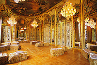 The ball room salle de bal ceiling painted by Solimena, baroque, 18th 18 th century. Hay bales seating, gilt and mirrors. At The Baccarat museum, shop, restaurant at the Hotel de Noailles in Paris. Designed by Philippe Starck. The ball room with its original seating: hay bales