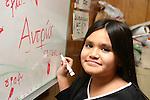 Lao/Greek girl writes Greek her name on a white board at Greek lanuage class in Long Beach, CA, USA.
