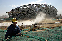 A Chinese worker works at the construction site of the National Stadium dubbed the Bird's Nest in Beijing, China. The stadium, designed by Herzog & de Meuron, will be at the heart of track and field competitions and the opening and closing ceremonies for the 2008 Beijing Olympics. .17 May 2007